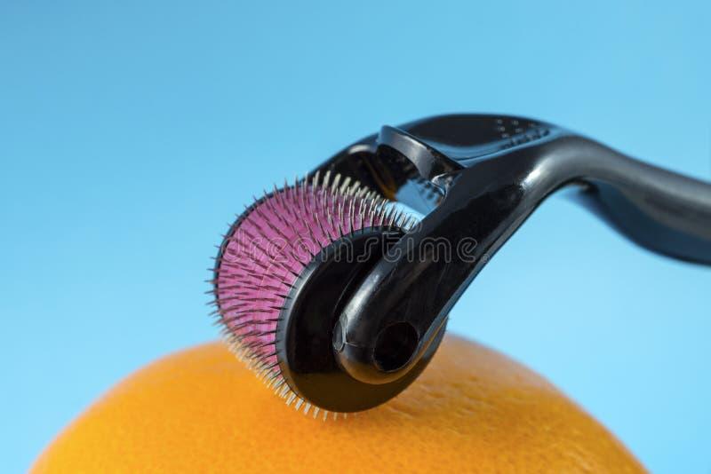 Rullo di Derma per la micro terapia medica di agugliatura con l'arancia fotografia stock libera da diritti
