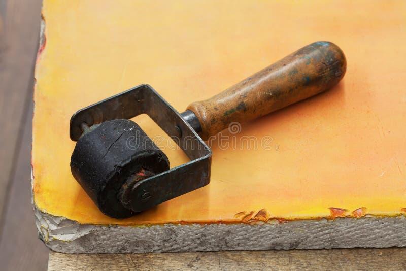 Rullo di gomma d'annata utilizzato per scritto tipografico, fondo di pietra arancio Strumenti di Diy, concetto degli accessori de immagine stock libera da diritti