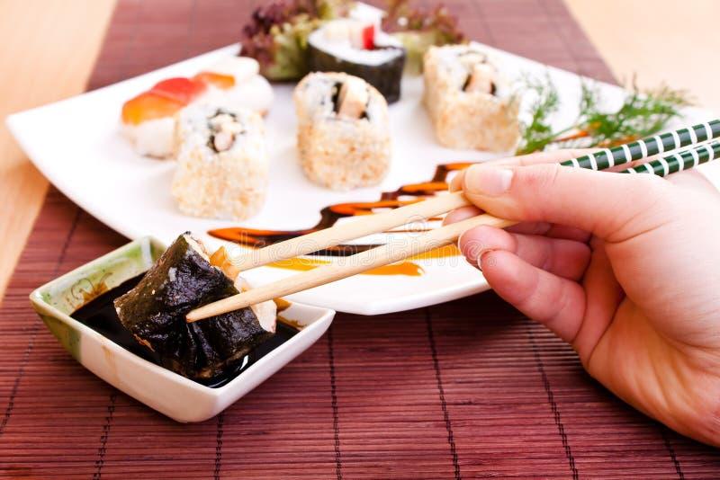 Rullo di sushi della holding con le bacchette fotografia stock