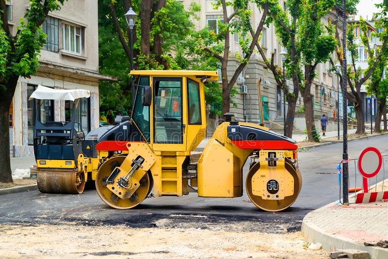 Rullo giallo per l'asfalto di pigiatura al sito degli impianti della costruzione di strade su una via della città un giorno di es fotografie stock