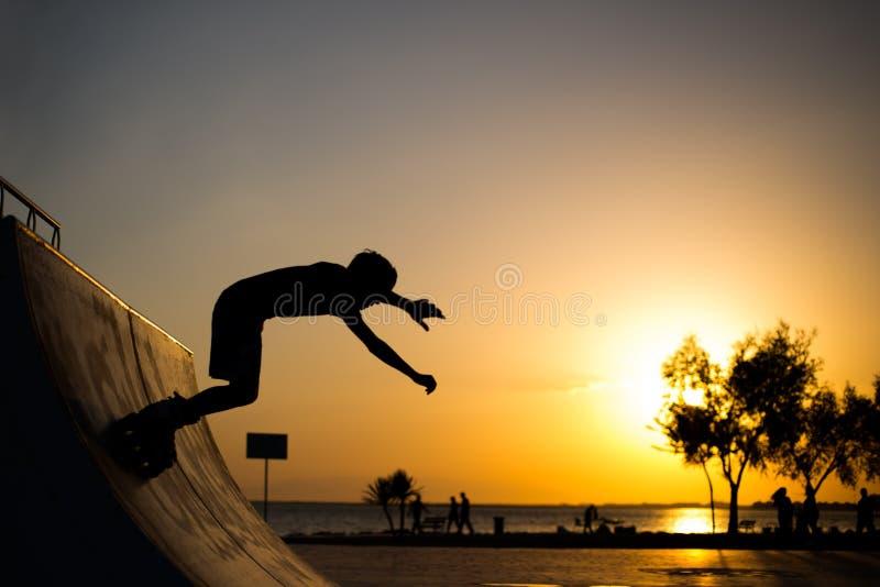 Rullskateboradåkaren hoppar royaltyfri bild