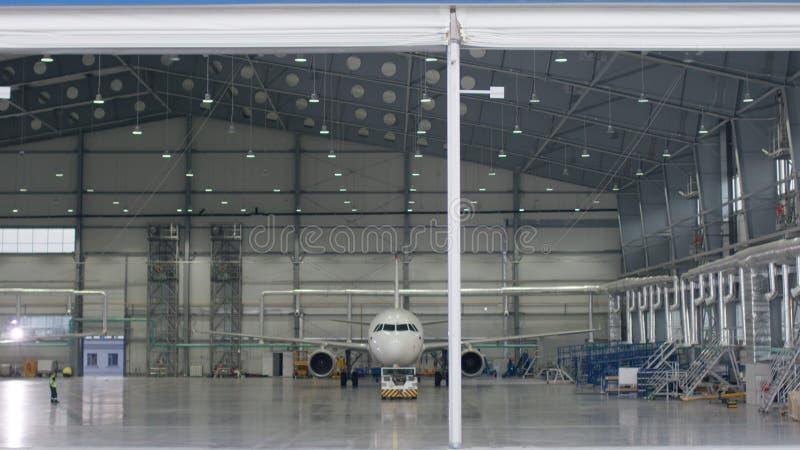 Rullslutaredörr och konkret golv av flygplatshangaren och flygplanbakgrund Flygplatshangar från yttersidan med fotografering för bildbyråer