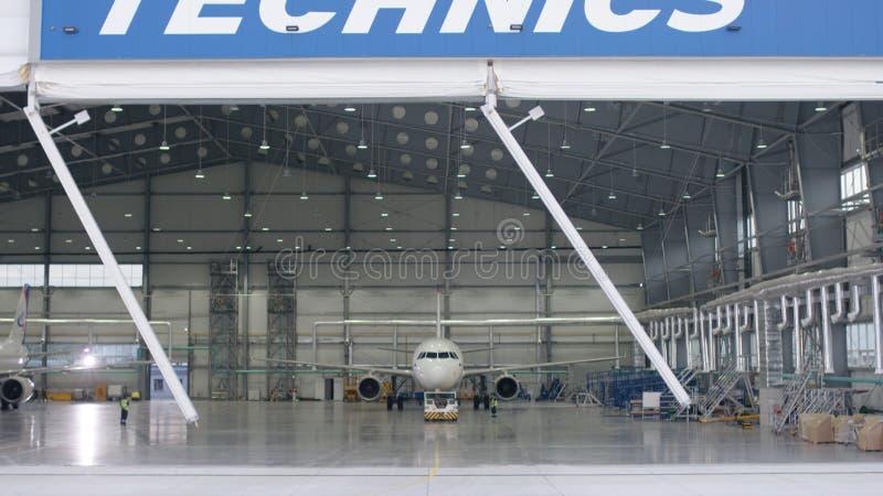 Rullslutaredörr och konkret golv av flygplatshangaren och flygplanbakgrund Flygplatshangar från yttersidan med arkivfoton