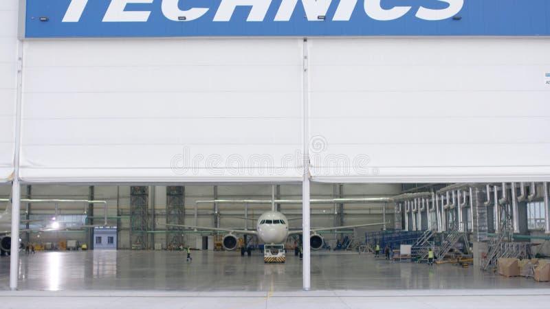Rullslutaredörr och konkret golv av flygplatshangaren och flygplanbakgrund Flygplatshangar från yttersidan med royaltyfri bild