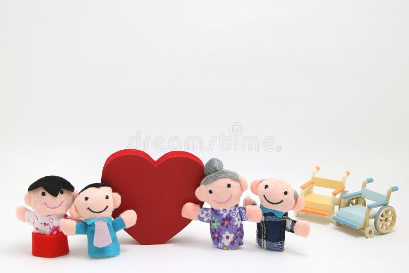 Rullstol, en stor röd hjärta och två-familjer på vit bakgrund arkivbilder
