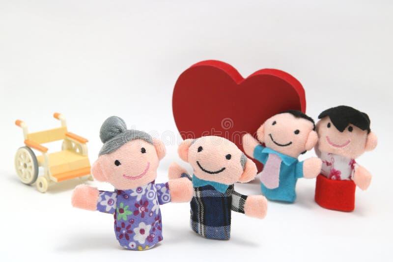 Rullstol, en stor röd hjärta och två-familjer på vit bakgrund royaltyfri fotografi