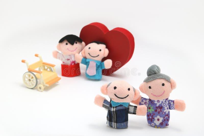 Rullstol, en stor röd hjärta och två-familjer på vit bakgrund royaltyfri foto