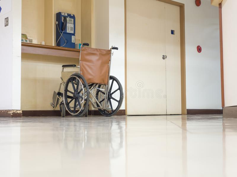 Rullstol som framtill parkerar av den blåa offentliga telefonen i sjukhus Rullstol som är tillgänglig för äldre eller sjukt folk royaltyfria foton