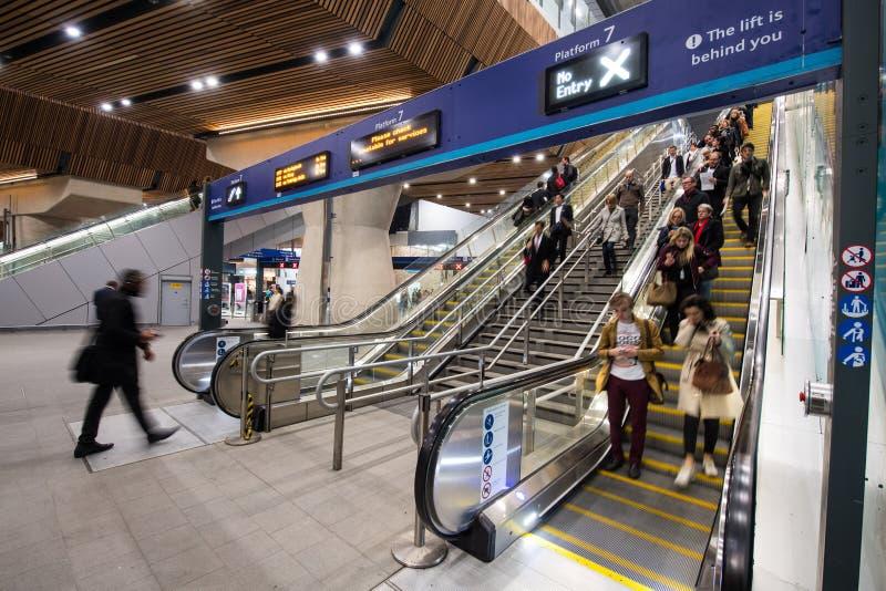Rulltrappor på den London brostationen royaltyfri foto