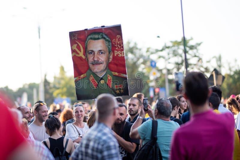 Rumänien Bucharest - Augusti 10, 2018: Personer som protesterar som visar en illustration av Liviu Dragnea som kommunist royaltyfri bild