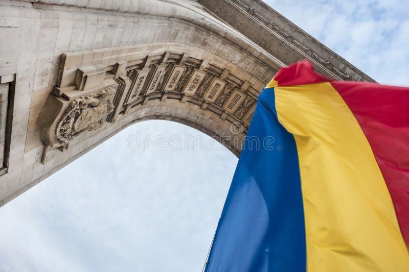 Rumänische Flagge, die am Triumphbogen in Bukarest hängt lizenzfreie stockfotos