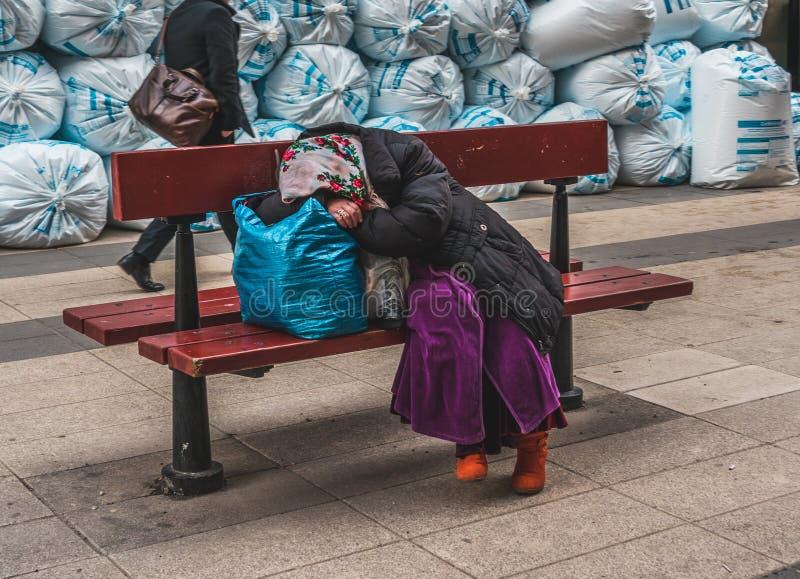 Rumänischer Bettler, der auf einer Bank mit ihrem Eigentum nach einem harten Tag des Bittens stillsteht stockfoto