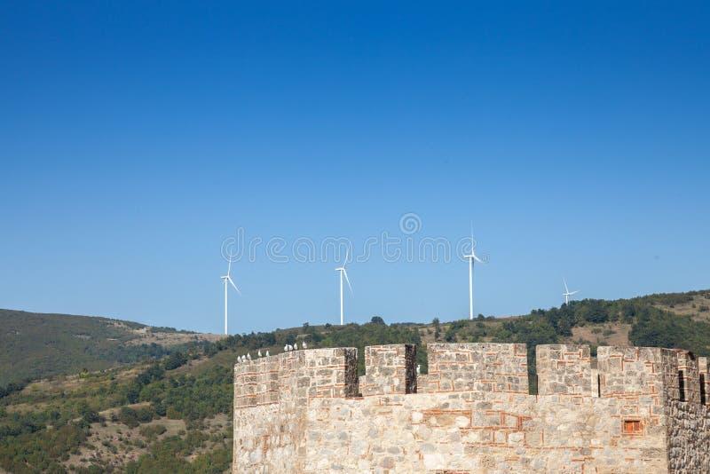 Rumänsk vindlantgård med vindturbinen och väderkvarnar som vänder mot en gammal slott som lokaliseras på den serbiska sidan av Da royaltyfri foto