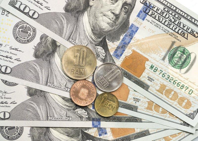 Rumänskt banimynt överst av dollarräkningar royaltyfria bilder