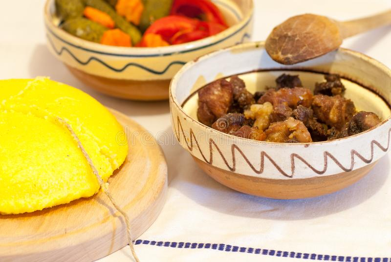 Rumänskt traditionellt vintersäsongmål med polentamamaliga stekte grisköttrester och gravade grönsaker arkivfoto