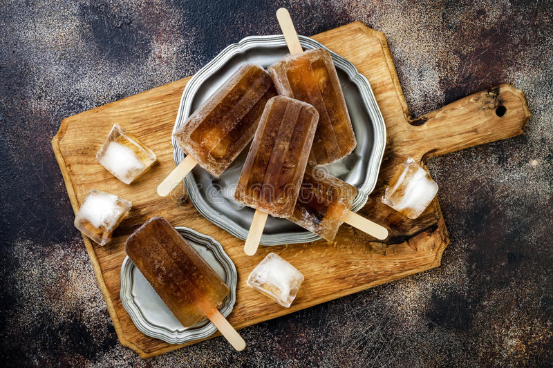 Rum and coke cocktail popsicles with lime juice. Cuba libre homemade frozen alcoholic paletas - ice pops. Overhead, flat lay. Top view, copy space stock images
