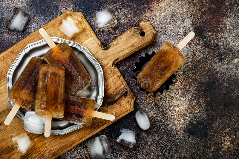 Rum and coke cocktail popsicles with lime juice. Cuba libre homemade frozen alcoholic paletas - ice pops. Overhead, flat lay royalty free stock images