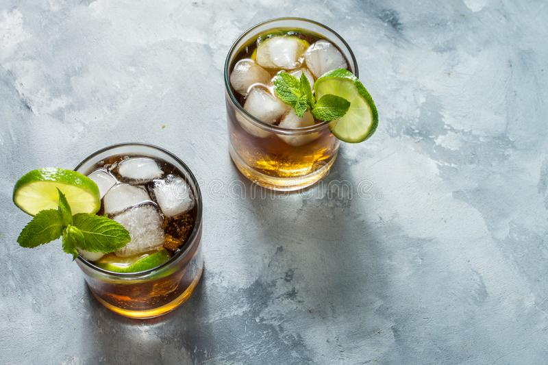 Rum and cola. Cuba Libre drink with lime and ice on rustic concrete table stock photos