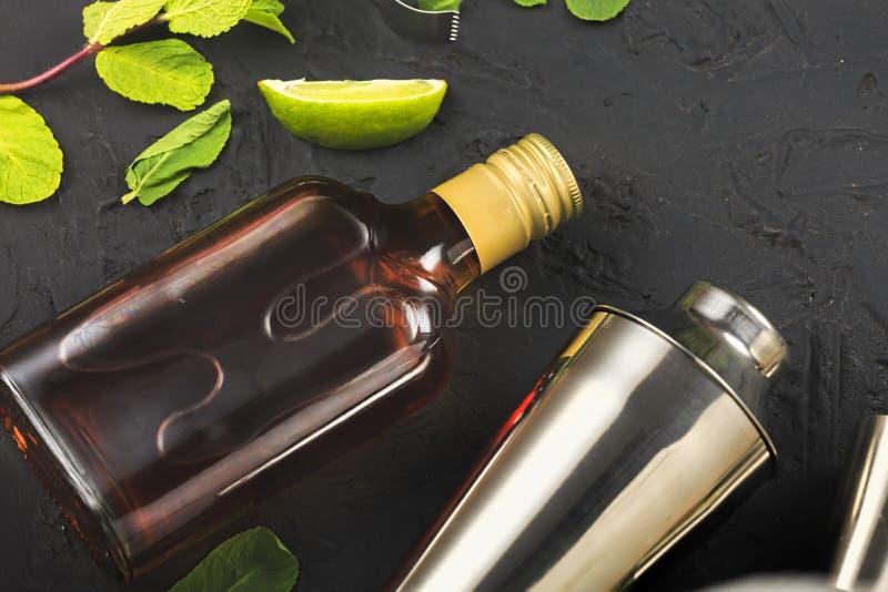 Rum, Cuba Libre, Fles donkere rum, Reeks, voor cocktail, steenachtergrond, zwarte achtergrond, rum, Fles, donkere rum, kalk royalty-vrije stock afbeeldingen