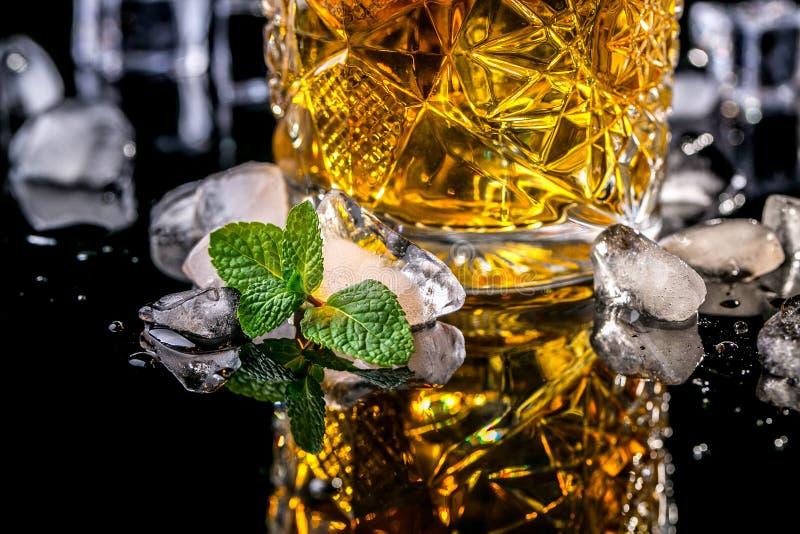 Rum e uísque do vintage da bebida do álcool com gelo e hortelã em um fundo preto da reflexão bebida luxuosa do conceito imagens de stock royalty free