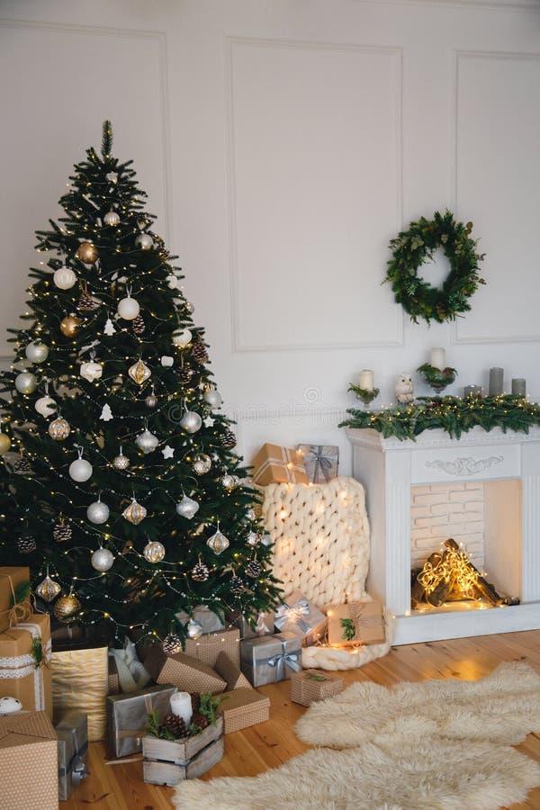 Rum för modern design för vindstil som dekoreras för vinterferie med det härliga julträdet, gåvor och gåvor, spis royaltyfri fotografi