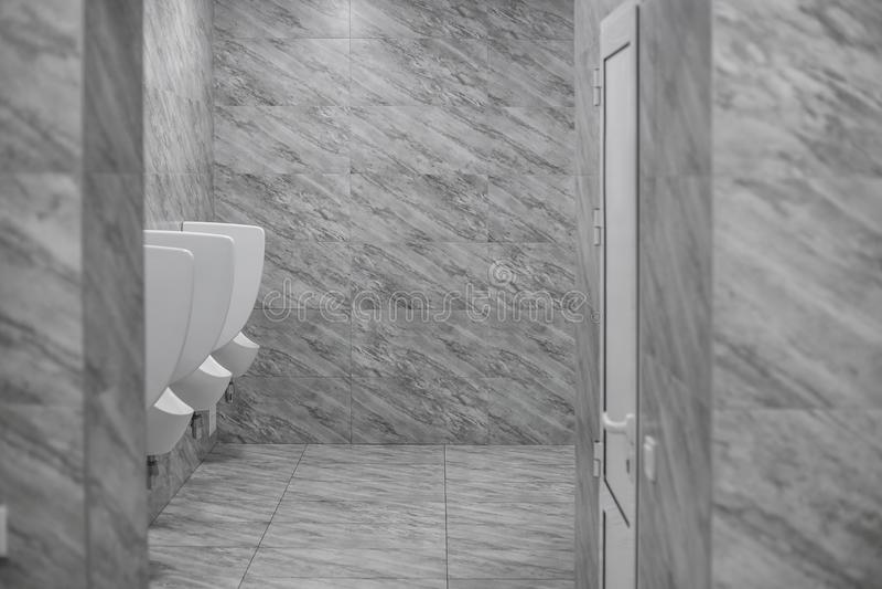 Rum f?r toalettman` s Nära övre rad av den offentliga toaletten för utomhus- pissoarmän, vita pissoar för Closeup i mäns badrum,  royaltyfri fotografi