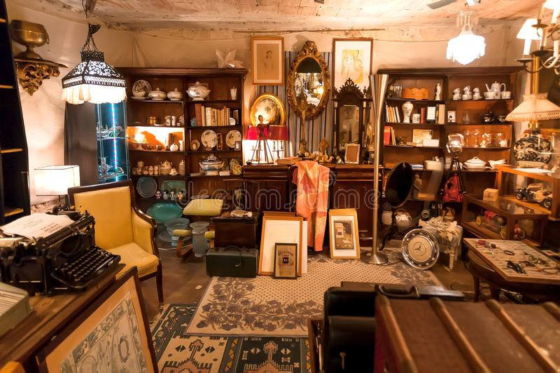 Rum med tappningmöblemang och färgrikt fyndmaterial, gammal dekor, retro redskap som är till salu på loppmarknaden arkivbilder