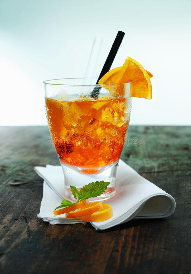 Rum and orange aperol spritz. Serving of aperol spritz cocktail with ice garnished with mint leaves and orange rind on a folded napkin on an old wooden counter stock photos