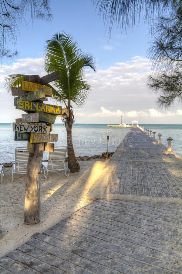 Rum Point Signpost and Dock. A signpost with various destinations next to the blue-green crystal clear waters off Rum Point dock on the north side of Grand royalty free stock photo