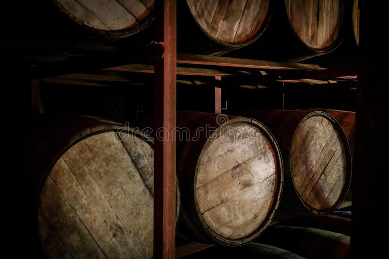 Rum or whiskey wooden barrels stacked in a warehouse.  stock photo
