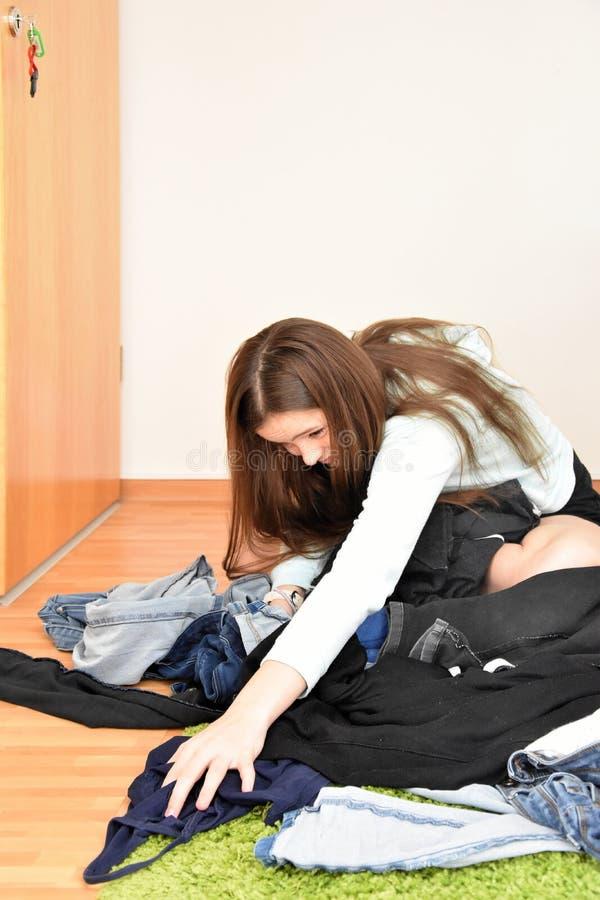 Rumages insoddisfatti dell'adolescente nel caos della sua attrezzatura fotografia stock