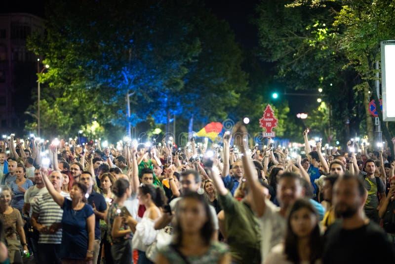 Rumania, Bucarest - 10 de agosto de 2018: Manifestantes que aumentan antorchas ligeras del teléfono en Victoria Square fotos de archivo libres de regalías