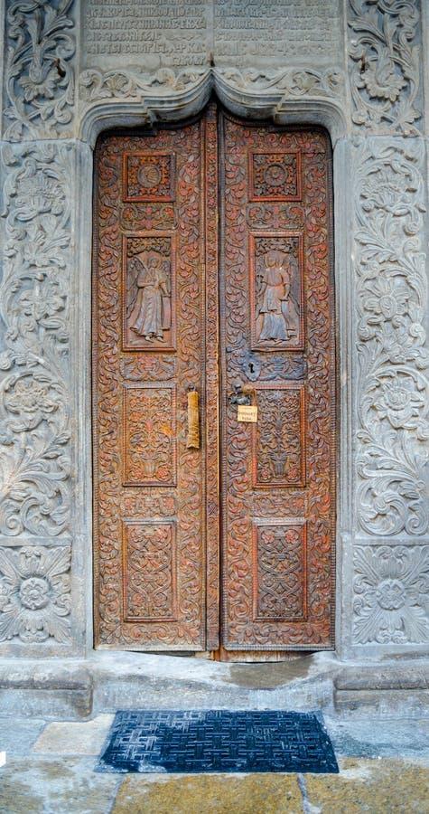 RUMANIA, Bucarest, puerta vieja de la iglesia con los santos esculpió en la madera imágenes de archivo libres de regalías