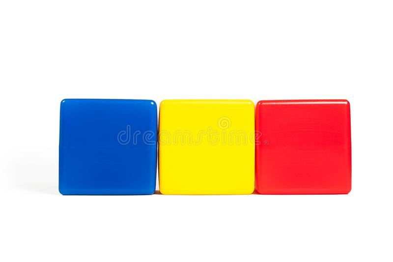 Rumania flag colors: blue, yellow, red in the form of children`s cubes. On white background isolated with shadow stock photography