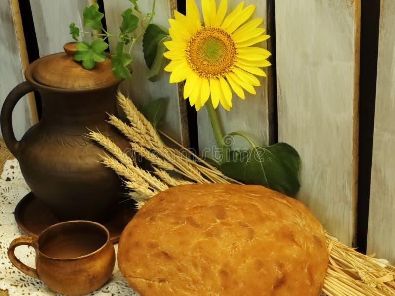 Rumianego żyta domowej roboty chleb, pszeniczni ucho, ceramiczny dzbanek i drewniane deski i jaskrawy żółty słonecznik na tle dla obrazy royalty free