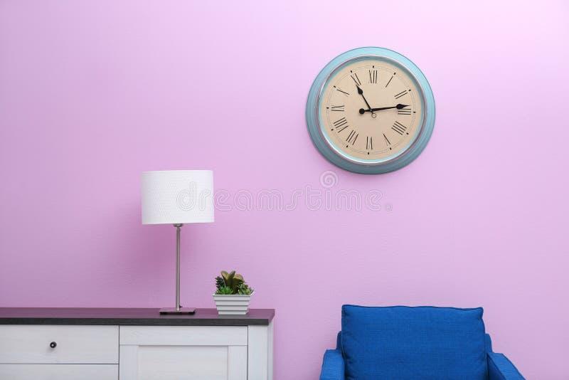 Ruminre med den stilfulla klockan på väggen royaltyfri bild