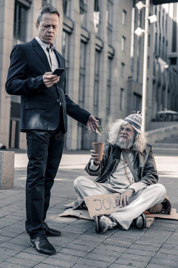 Rumsren affärsman i dräkten som sätter pengar i kaffekopp royaltyfri foto