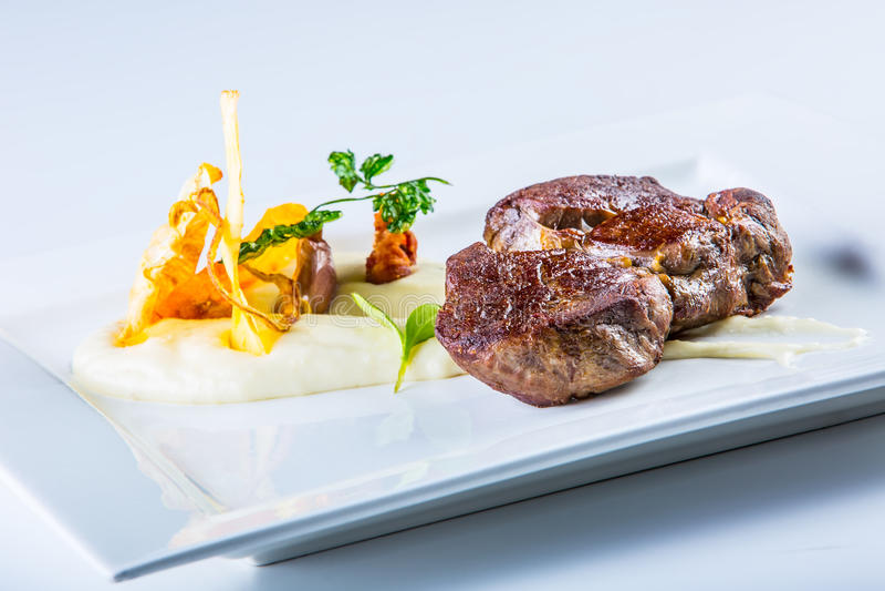 Rumsteak Fermez-vous vers le haut de la viande de boeuf grillée par offre du plat blanc avec la décoration végétale image libre de droits