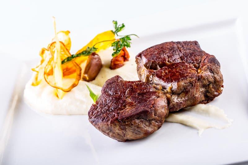 Rumsteak Fermez-vous vers le haut de la viande de boeuf grillée par offre du plat blanc avec la décoration végétale photographie stock libre de droits