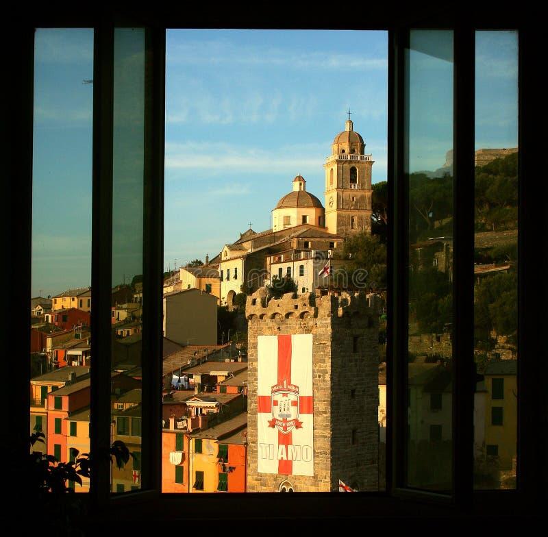 Rumvandrarhemmet med fönstret som förbiser byggnaderna, står högt och domkyrkan av Portovenere royaltyfri foto