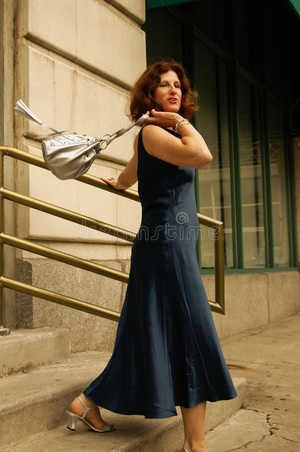 On the run. Mature woman with handbag flung over her shoulder. She's desending stairs and looking directly into the camera royalty free stock photography