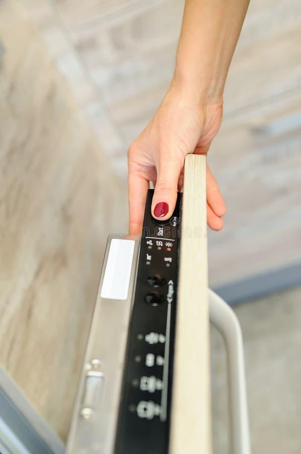 Run the dishwashing machine. Woman`s finger pressing the Start button stock photography