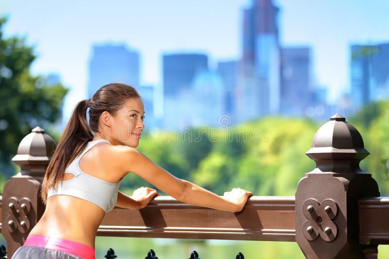 Run exercise jogging woman stretching in central park, New York City, Manhattan NYC. Stretch. For legs royalty free stock photos