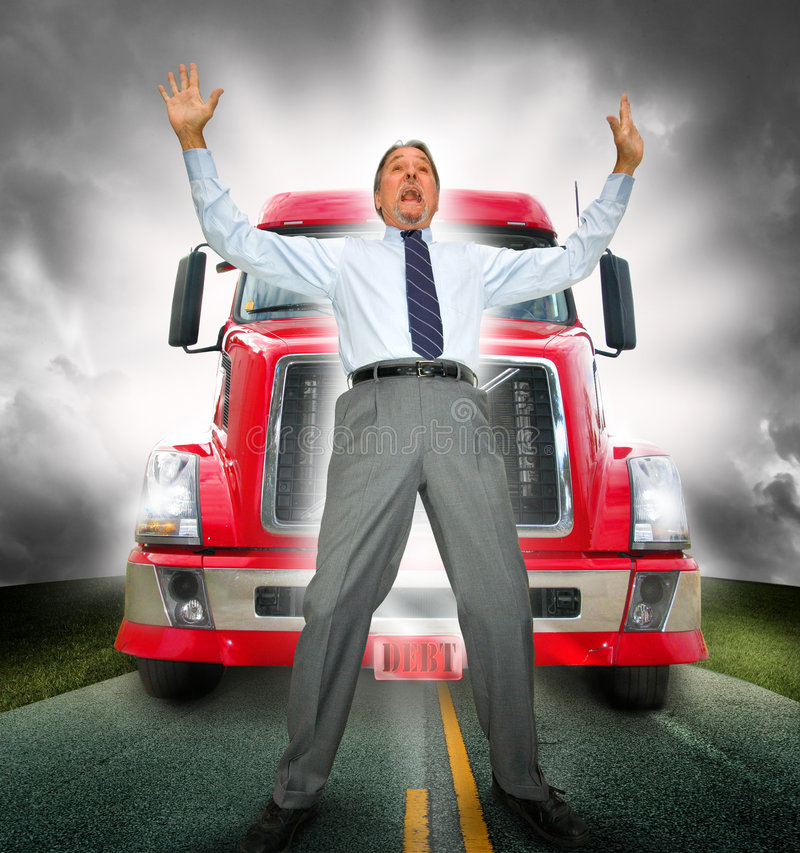 Run over by debt. A man in a tie stands in alarm as a big red semi truck comes from behind on an asphalt road. Concept for current money and debt issues of stock images