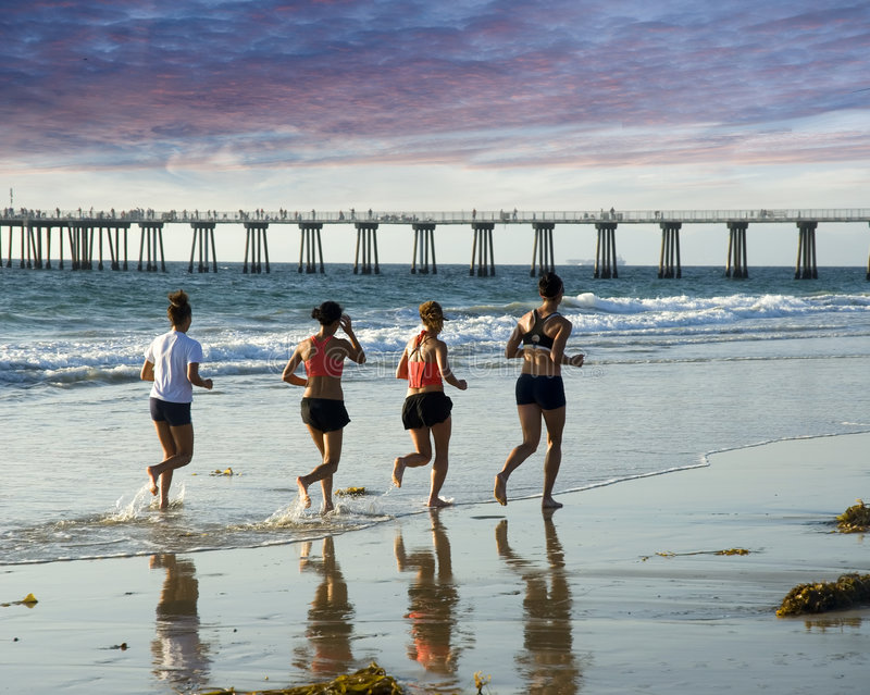 A run to the pier. Four women are seen jogging along the waters edge for exercise royalty free stock image