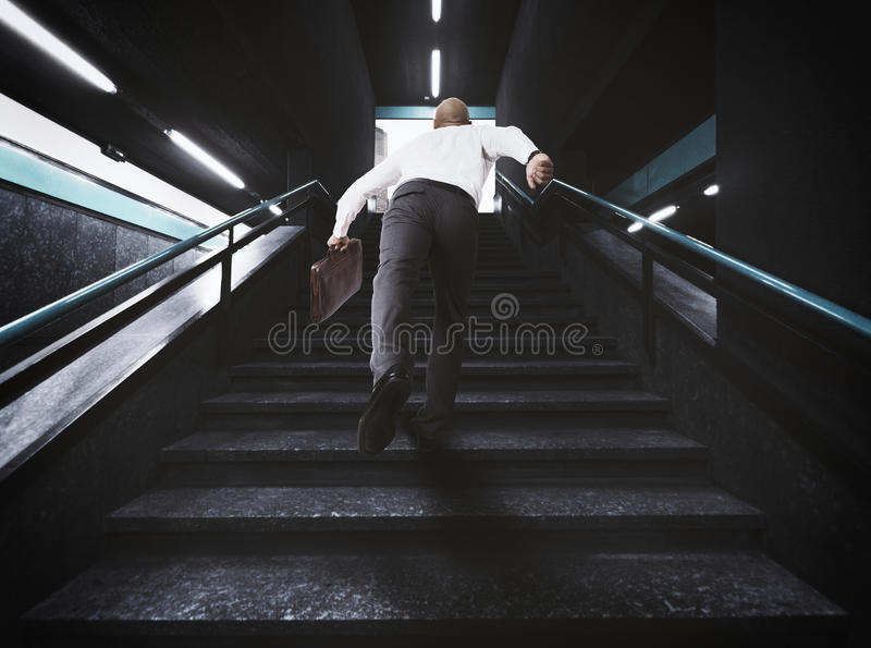 Run to work. Delayed businessman with bag runs on the stairs royalty free stock photo