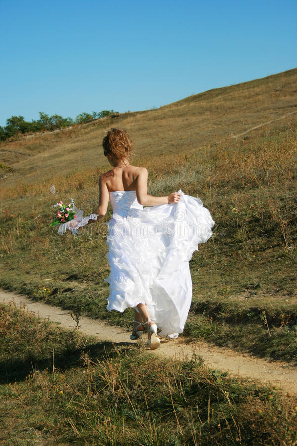 Runaway bride. Bride running to the new life stock image