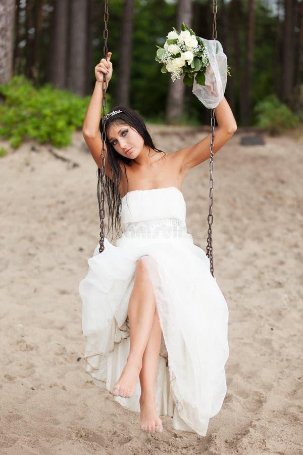 Runaway bride. Sitting on a swing stock photo