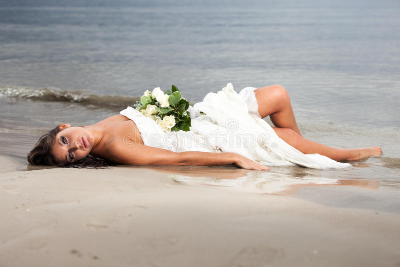 Runaway bride. Laying in the sea royalty free stock image