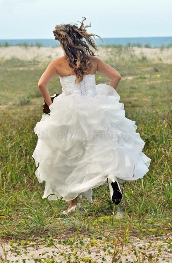 Runaway Bride. This Runaway Bride is leaving the groom at the alter or in this case , on the seashore stock image